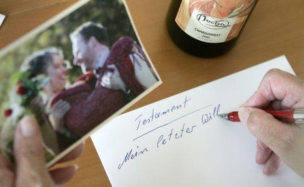 Eine Person verfasst handschriftlich auf einem Blatt Papier ein Testament.